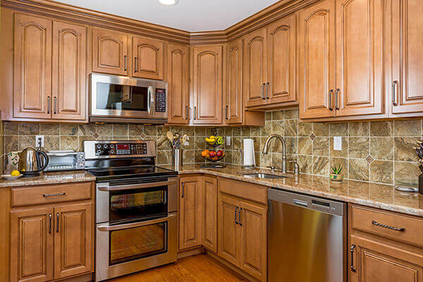 Kitchen in luxury home with mocha wood cabinetry